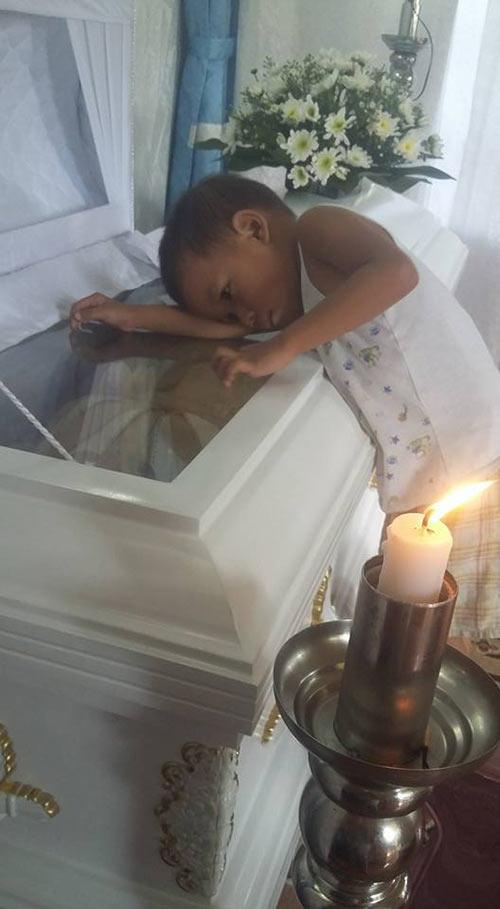 Hình ảnh bé trai bơ vơ ôm quan tài mẹ khiến triệu trái tim quặn đau - 1
